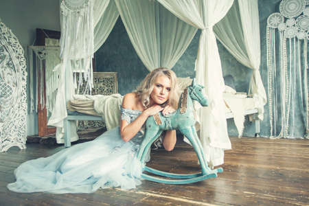Magnificient woman in blue tulle dress in luxurious vintage interior portrait Standard-Bild