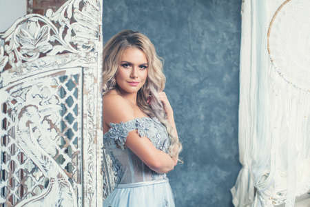 Beautiful female portrait. Perfect blonde woman looking at camera and posing in vintage interior Reklamní fotografie