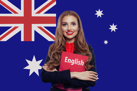 Happy smiling woman student with book against Australian flag Stockfoto