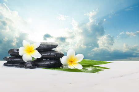 Tropical flowers and black stones ready for healthy therapy and clouds with sunlight. Health objects on white marble table