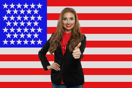 Portrait of happy american girl with thumb up against the USA flag. Travel and learn english language concept Foto de archivo