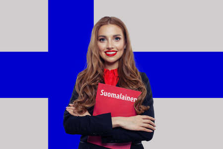 Young woman smiling and posing against the Finnish flag background. Finnish language school and travel concept. Book with inscription Finnish on finnish language Stockfoto
