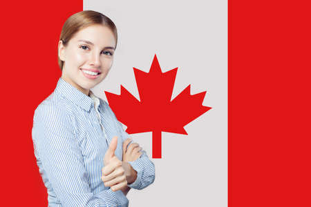 Cute young woman showing thumb up against the Canada flag. Live, work, education and internship in Canada