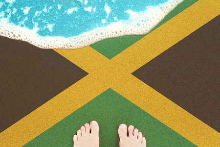 Feet on the sunny sandy beach with flag Jamaica. View from top on surf.