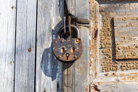Old padlock on a wooden door. Heavy granary iron lock.