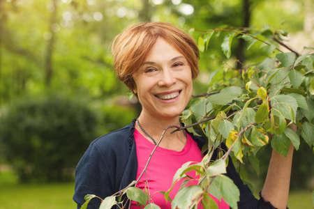 Gesunde reife Frau, die Spaß mit den grünen Blättern im Freien hat. Schönes Model 60 Jahre alt