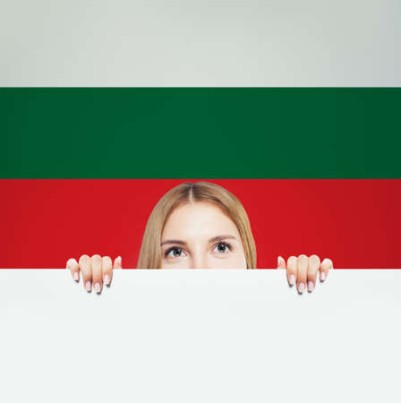 Love Bulgary concept. Happy woman showing white paper against Bulgarian flag