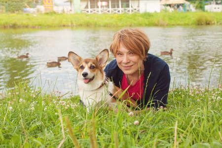 Pretty senior woman lying on green grass and hugging her corgi dog