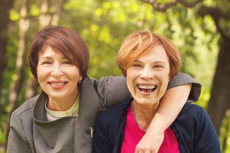 Two happy women walking in summer park, portrait