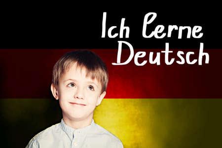 Thinking child boy student against the Germany flag background. Deutsch concept with inscription learn Deutsch on Deutsch language Reklamní fotografie