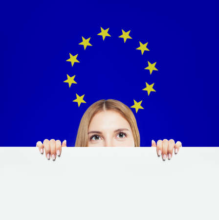 Happy woman showing white  against the EU flag
