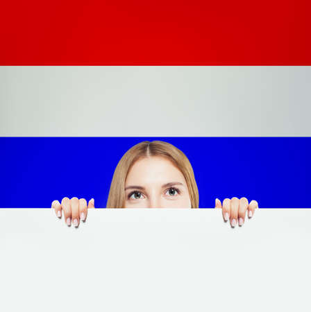 Love Netherlands! Happy woman smiling and showing white banner on netherlandish flag