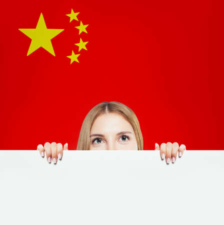 Happy woman with white  against the Peoples Republic of China flag