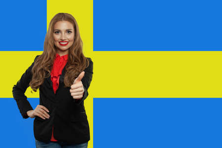 Sweden. Happy cute student girl with thumb up against the Sweden flag Stockfoto