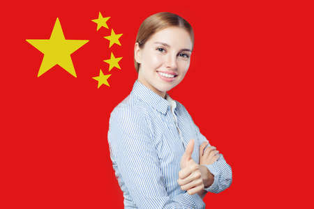 Happy woman with thumb up against the Peoples Republic of China flag