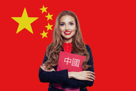 Beautiful smiling woman with flag of China. Book with inscription Chinese on Chinese language Stockfoto