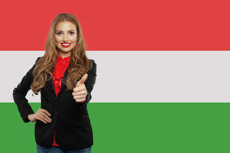 Happy cute student girl against the Hungary flag background. Study hungarian language Stok Fotoğraf
