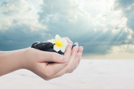 Mnicured hands with natural french nails and tropical spa objects. Healthy concept with clouds sky and sunlight