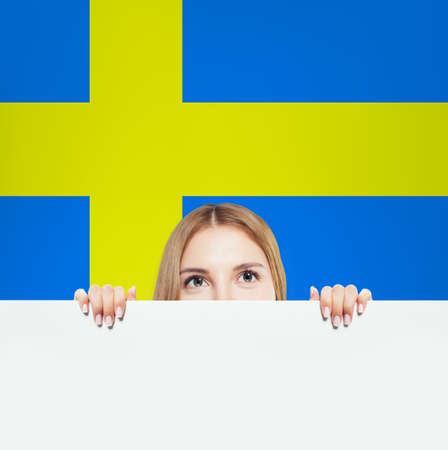 Sweden. Happy student girl with white banner against the Sweden flag background. Travel and learn Sweden language Stok Fotoğraf