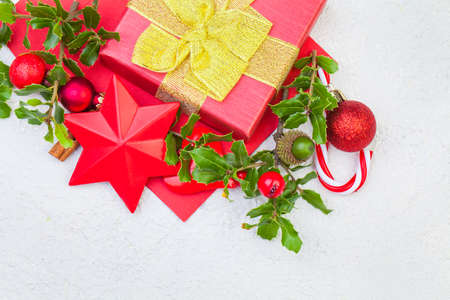 Christmas composition. Xmas gift box, holly berries and red decorations