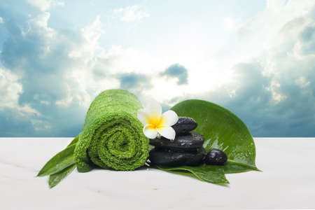 Spa set with towel and flower for wellness therapy. Spa healthy concept with clouds sky and sunlight.