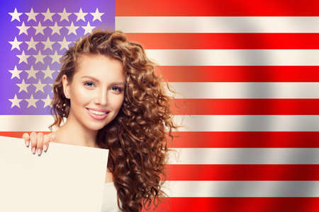 Happy american girl with white paper against the USA flag background. Travel and learn english language concept Фото со стока