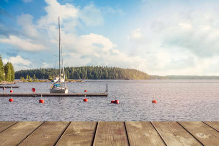 Yacht near the wooden mini pier on Lake in Finland. On a summer evening Banco de Imagens