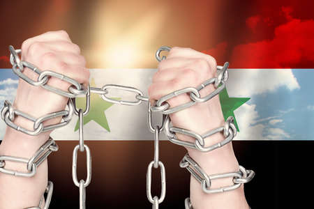 Two hands shackled a metal chain on the Syria flag. Freedom concept
