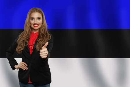 Estonia. Happy girl showing thumb up and smiling on Estonian flag 版權商用圖片