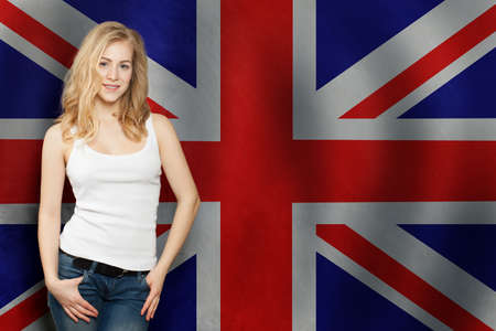 Portrait of happy blonde pretty girl with UK flag background. Фото со стока