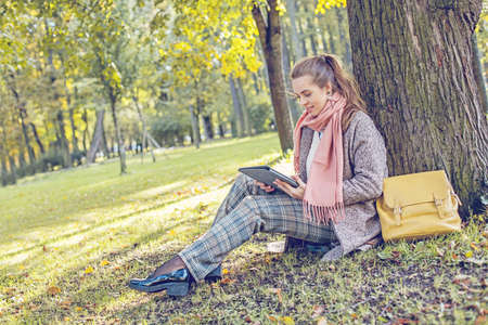 Cute businesswoman with tablet laptop at work outdoors in park