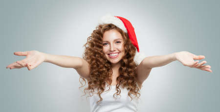 Happy excited young woman in Santa hat smiling. Christmas and New Year party