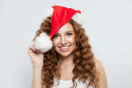 Happy young woman in Santa hat smiling on white Фото со стока