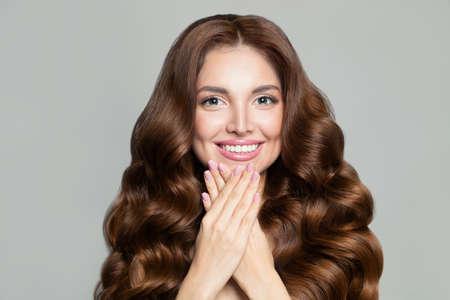 Beautiful woman with long healthy brown curly hair Фото со стока