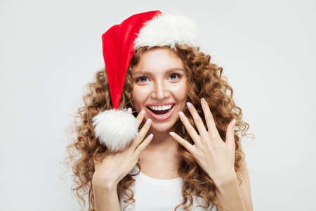 Happy excited surprised young woman in Santa hat smiling. Фото со стока