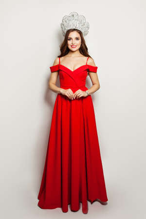 Elegant woman in red dress and diamond crown standing on white