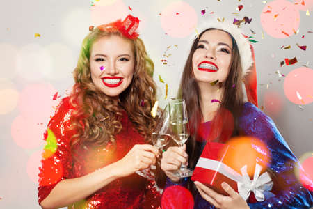 Christmas women laughing. Winter fashion model girls on abstract bokeh glitter sparkle party Фото со стока