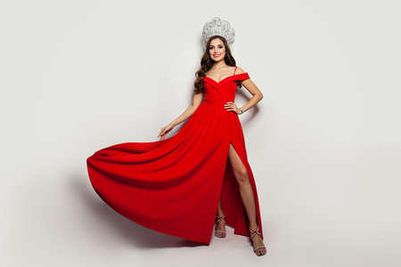 Fashion portrait of beautiful woman wearing red blowing dress and diamond crown on white