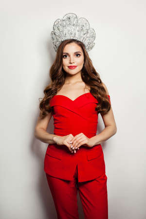 Beautiful model woman in red suit and diamond crown standing on white background Фото со стока