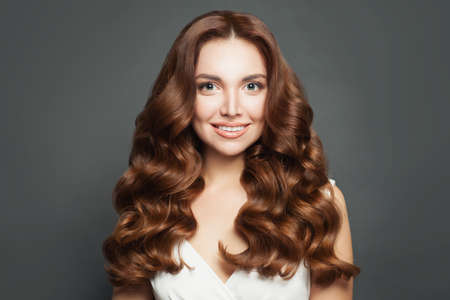 Beautiful woman with long healthy brown curly hair smiling Фото со стока
