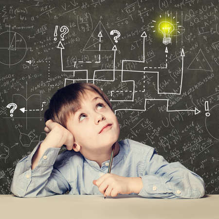 Thinking child boy with question signs and light idea bulb, education concept with math formula Фото со стока