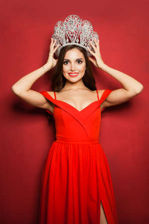 Pretty model girl wearing red dress and diamond crown on red background