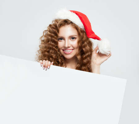 Christmas woman in Santa hat holding white empty singboard card