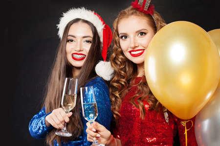 Christmas pretty happy women models in party dress on black background Фото со стока