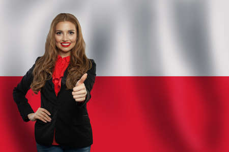 Cute young woman showing thumb up on the Poland flag background.