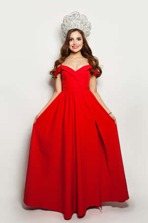 Fashion model woman in red blowing dress and diamond crown on white background.