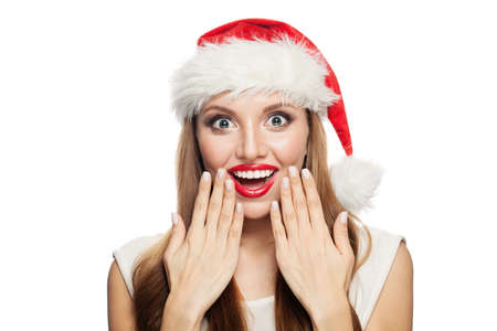 Happy surprised Christmas woman in Santa hat isolated on white background.
