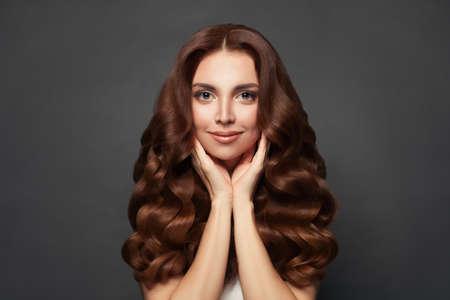 Beautiful cheerful woman with long curly hair. Фото со стока