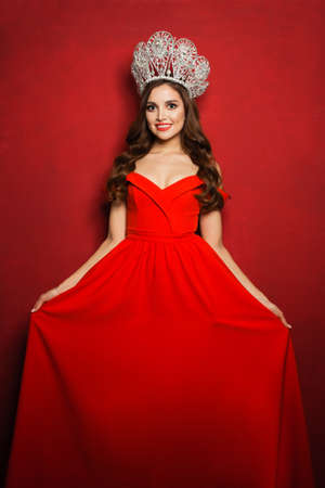 Beautiful woman in red dress and diamond crown
