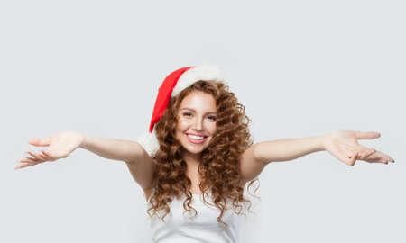 Beautiful woman in Santa hat having fun on white background